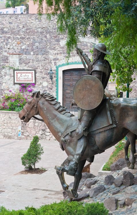 A statue of Don Quixote and the front of the Cervantes Theater.