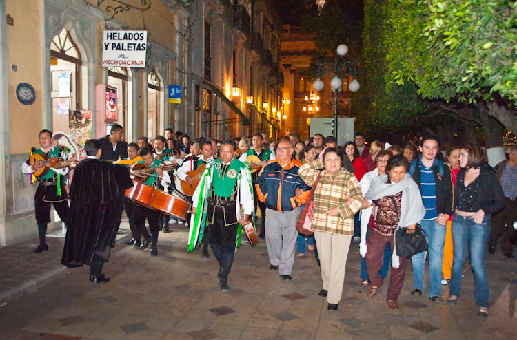 A traditional pastime, musical groups lead people through the streets singing.