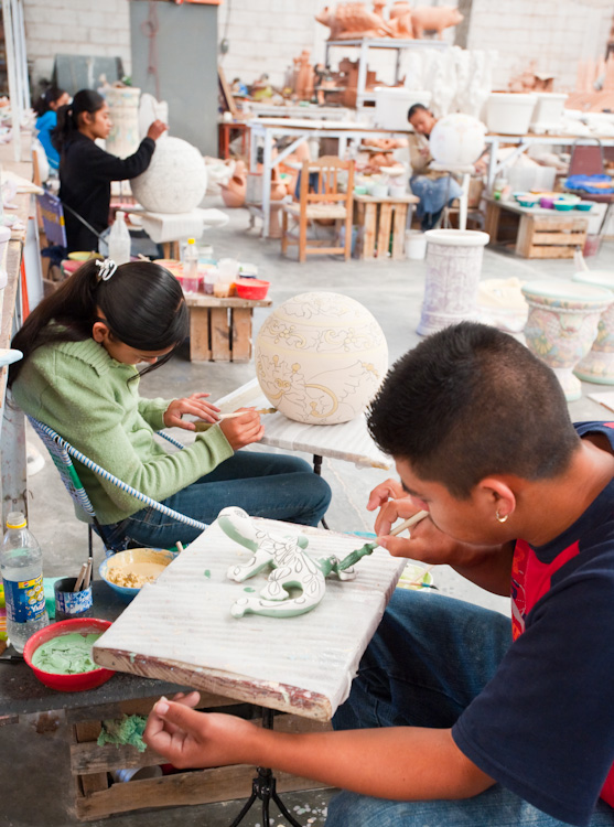 Artists decorating ceramics prior to firing.